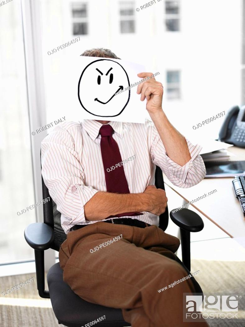 Stock Photo: Businessman holding picture of angry face.