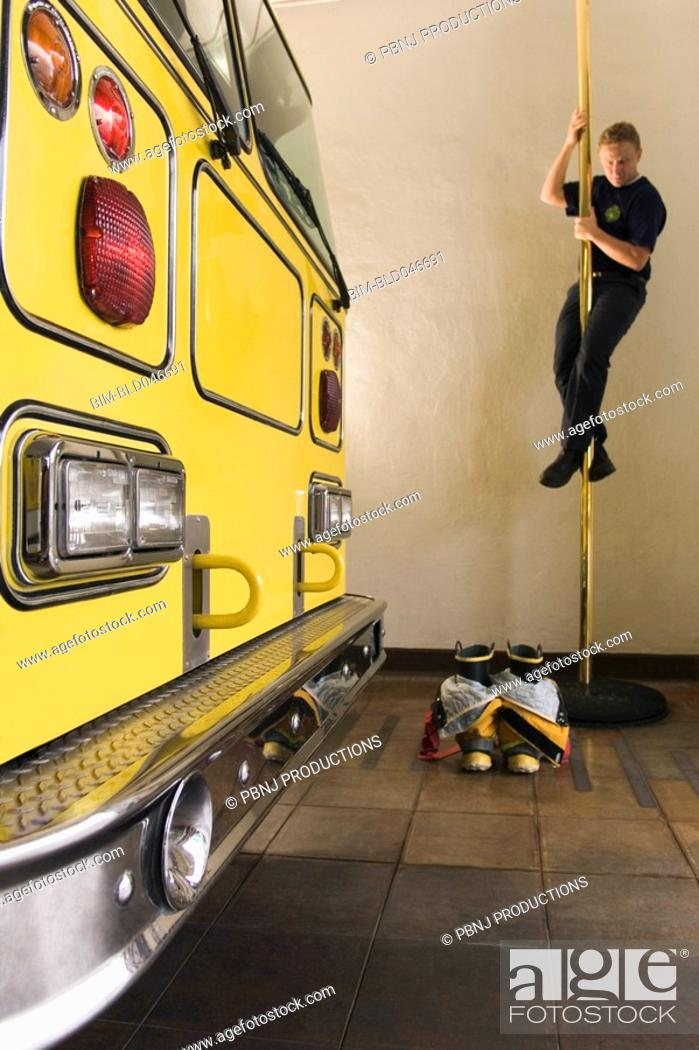 Stock Photo: Male firefighter sliding down pole.