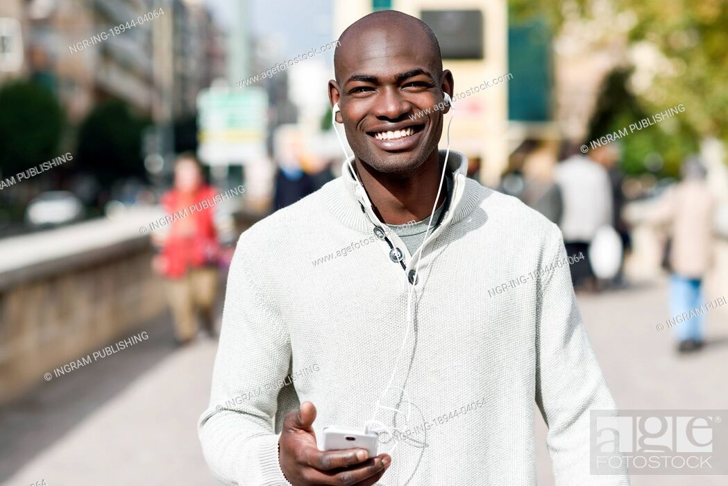 Stock Photo: Black young man with a smartphone in his hand in urban background. Young african guy with shaved head wearing casual clothes and white headphones.