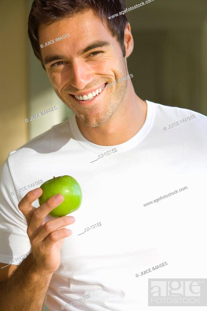 Stock Photo: Young man with apple, smiling, portrait, close-up.