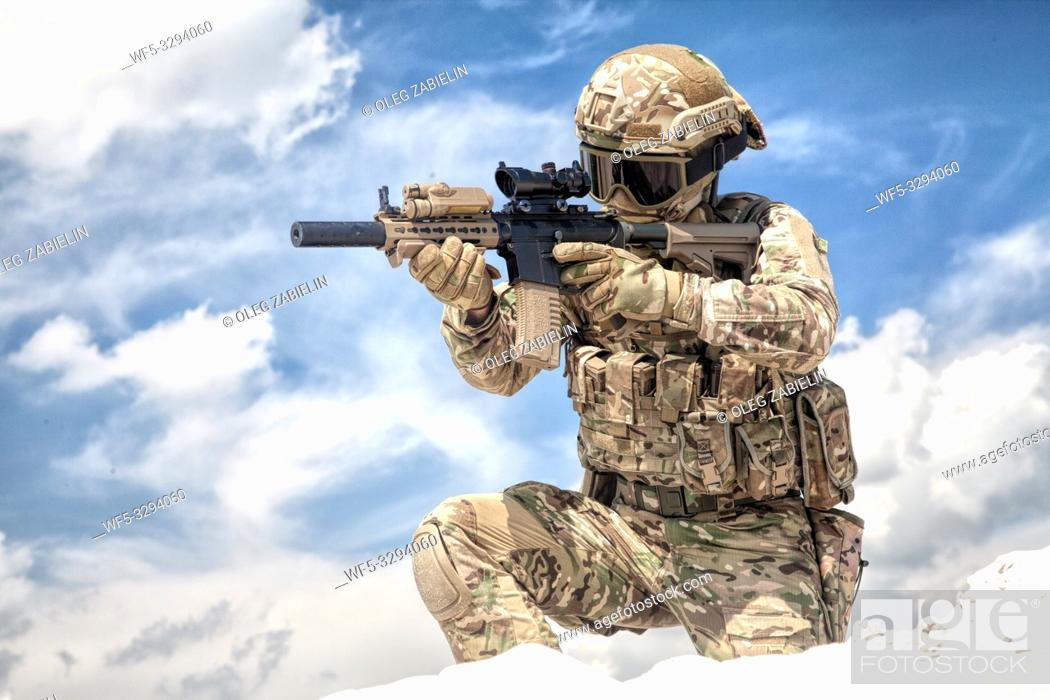 Stock Photo: Fully equipped with tactical ammunition airsoft player in military camouflage uniform, aiming with optical sight on service assault rifle replica while stand on.