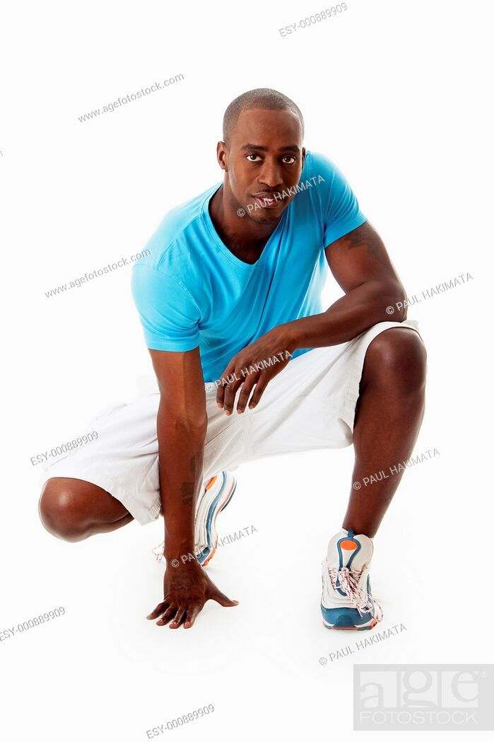 Stock Photo: Handsome African American sporty man crouching wearing blue shirt, isolated.