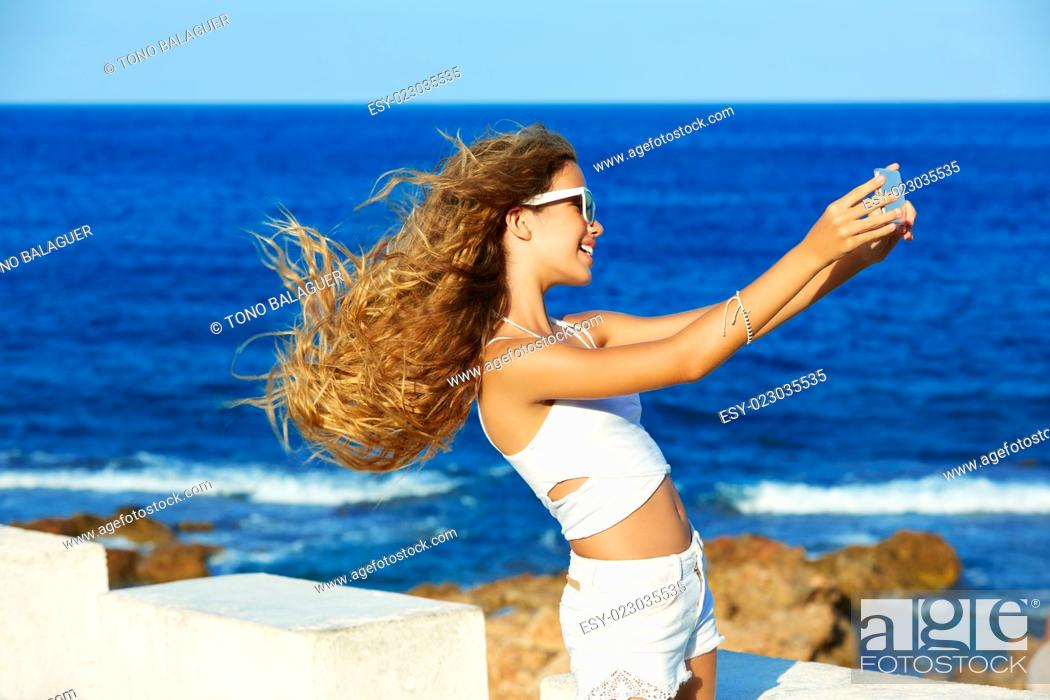 Imagen: Blond kid teen girl photo selfie on smartphone in a beach at Mediterranean.