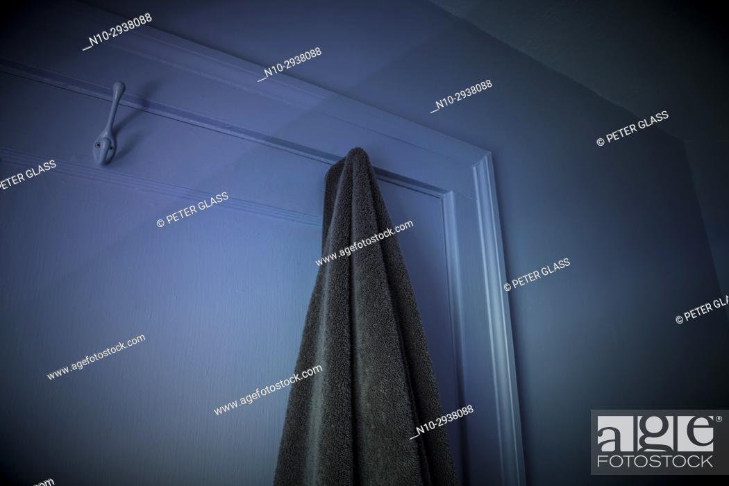 Stock Photo: Bath towel hanging on hook on closed bathroom door.