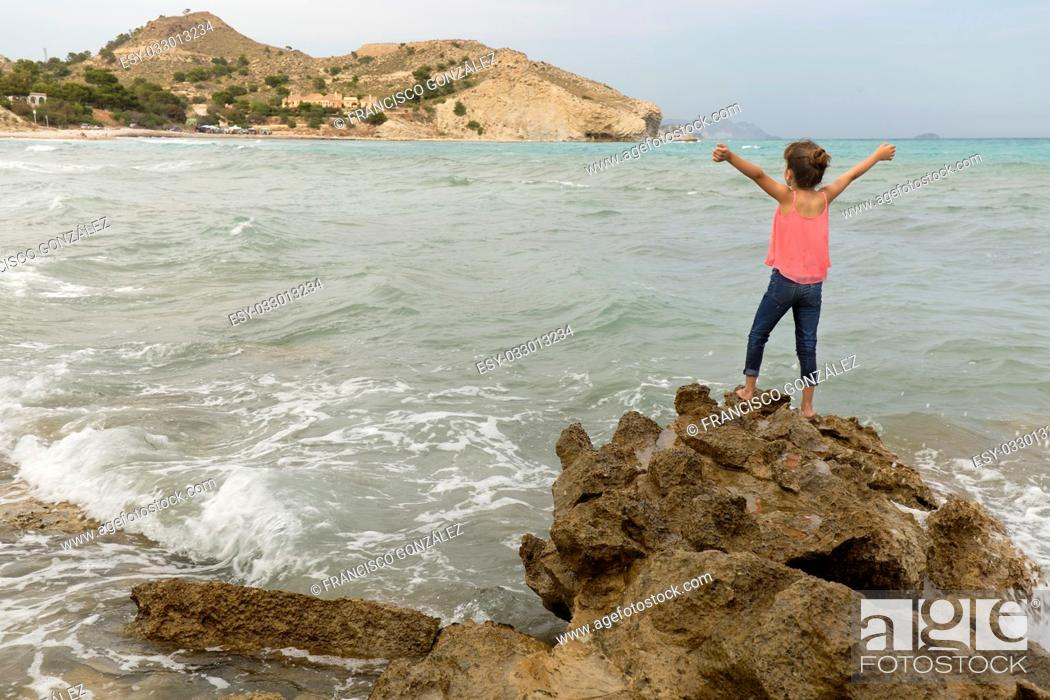Photo de stock: Girl with arms raised on the rocks of a creek of Villajoyosa, in the province of Alicante, Spain.