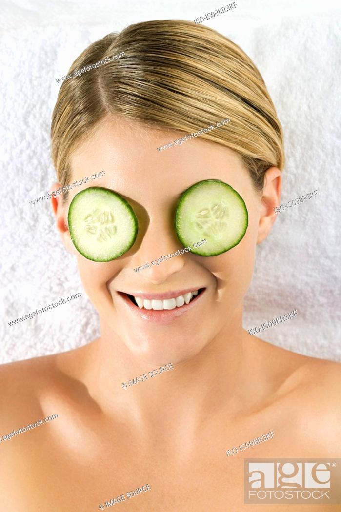 Stock Photo: Smiling young woman lying on towel with cucumber slices over eyes.