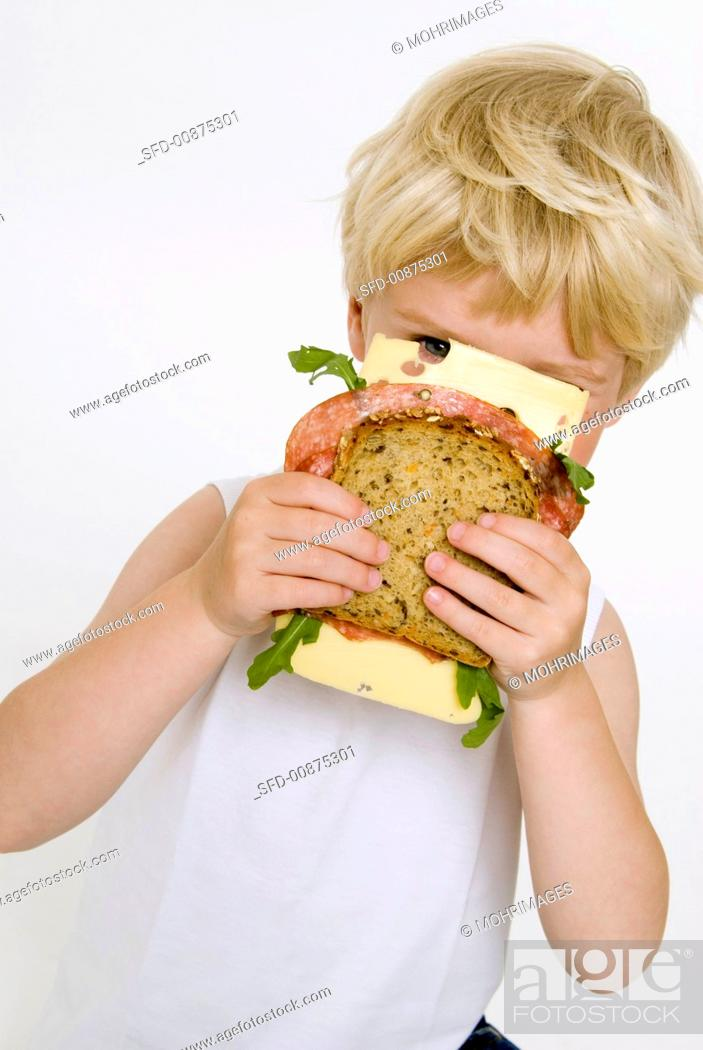 Stock Photo: Blond boy holding salami & cheese sandwich in front of his face.