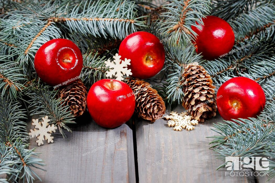 Imagen: Red apples and fir branch with cones on wooden table. Christmas background, copy space.