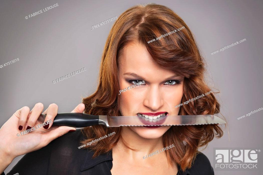 Stock Photo: Young woman with knife between teeth.