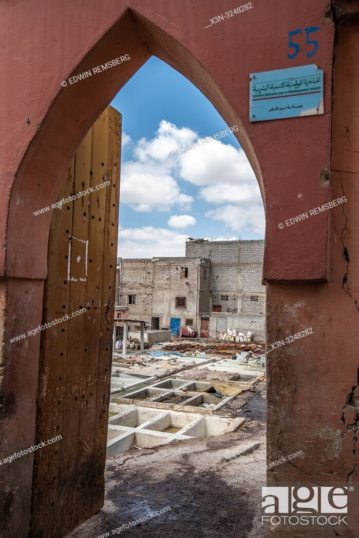 Stock Photo: View through arch of doorway leading to pits full of solutions used to convert animal hides into tanned leather at tannery, Marrekech, Morocco.