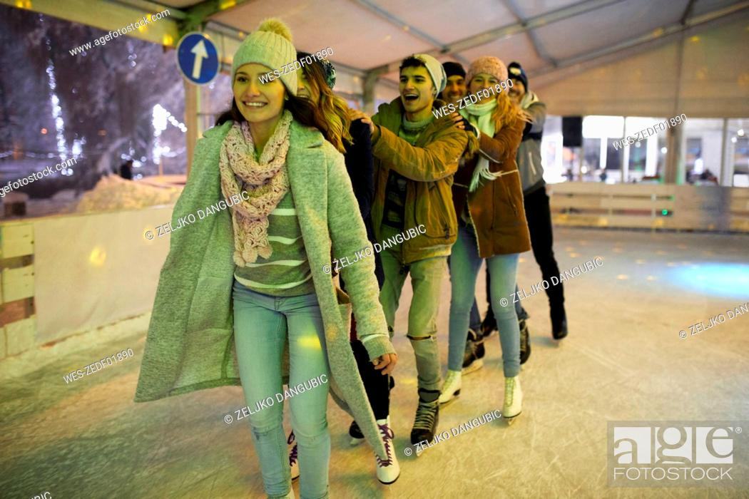 Stock Photo: Happy friends ice skating on an ice rink at night.