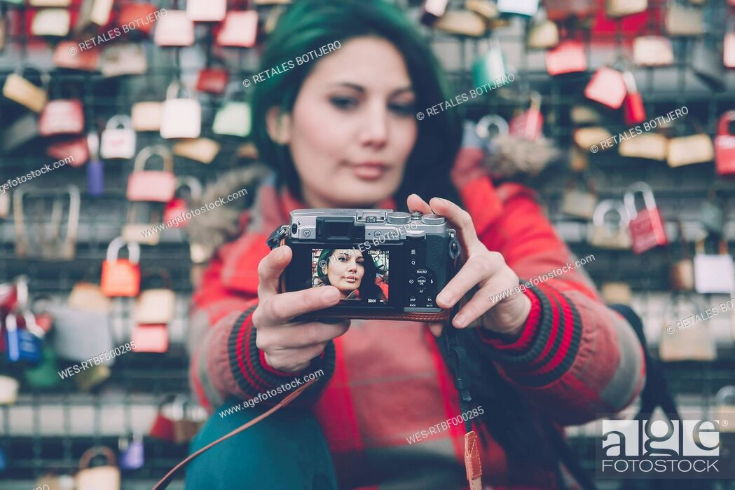 Stock Photo: Germany, Cologne, woman taking selfie in front of love locks at Hohenzollern Bridge.