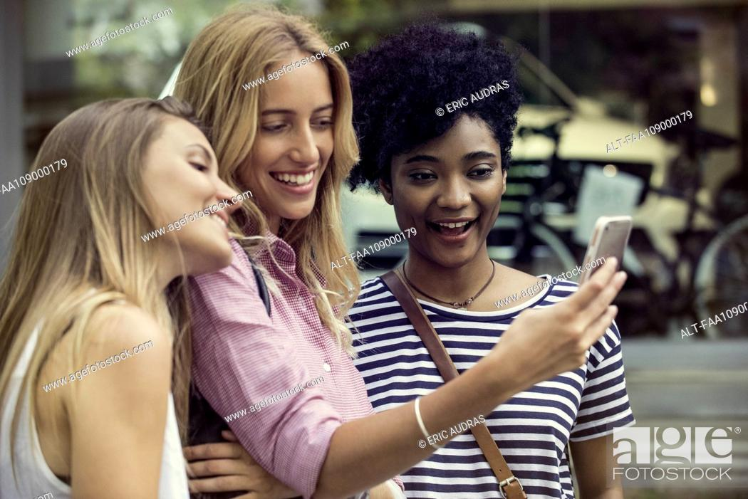 Stock Photo: Friends using smartphone to take a selfie.