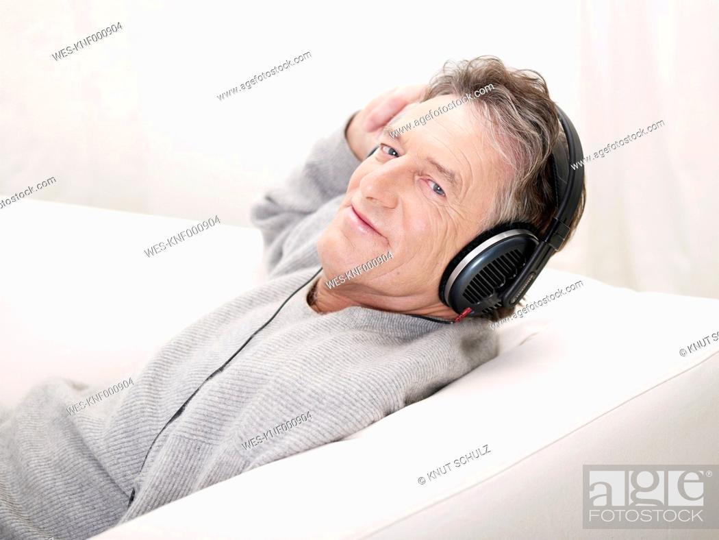 Stock Photo: Germany, Hamburg, Senior man listening music, portrait.