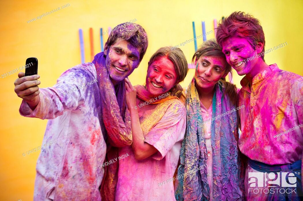 Stock Photo: Friends taking picture of themselves with a mobile phone during Holi.