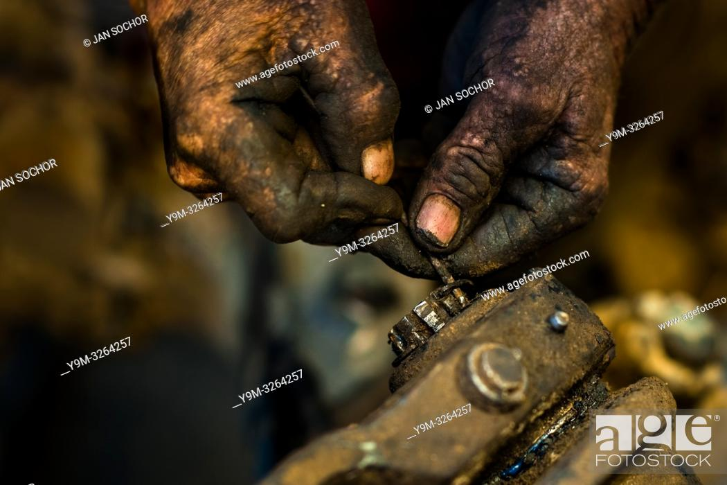 Stock Photo: A Colombian car mechanic works on an axle while performing maintenance on a truck in Barrio Triste, Medellín, Colombia, 28 November 2017.
