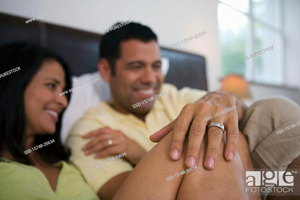 Stock Photo: Close-up of a mature couple reclining in the bed and smiling.