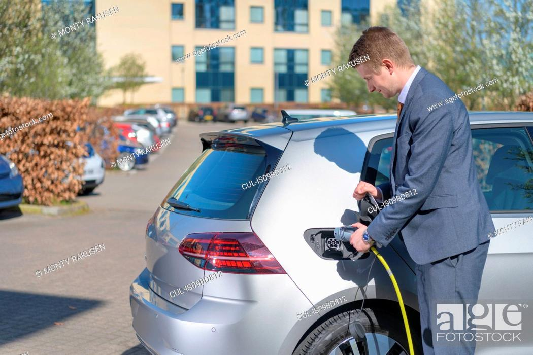 Stock Photo: Businessman charging electric car at charging point in business park.