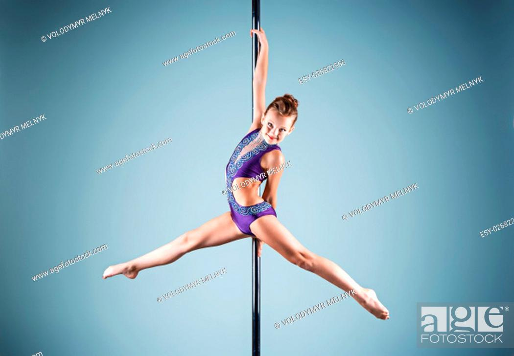 Imagen: The strong and graceful sports young girl performing acrobatic exercises on pylon on blue background.