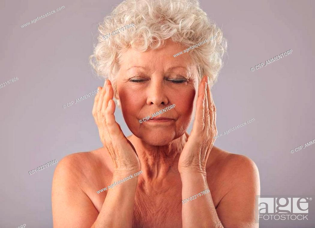 Imagen: Old woman touching her face.