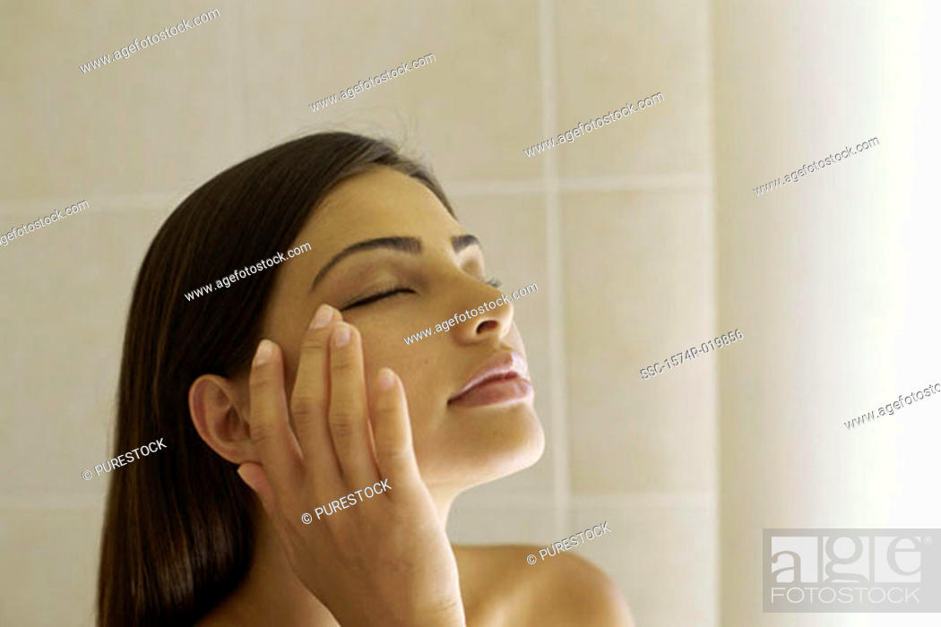 Stock Photo: Close-up of a young woman touching her face.