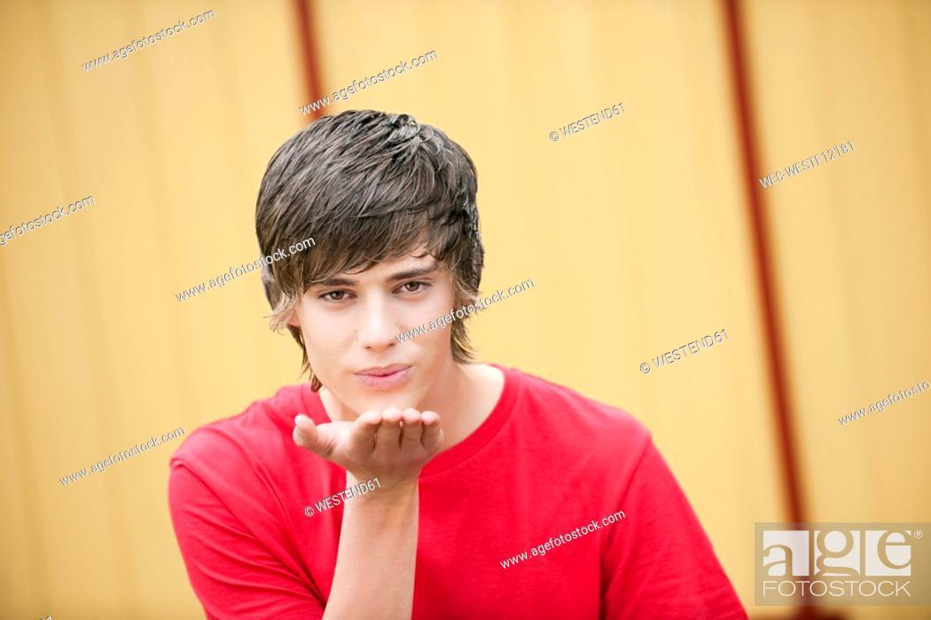 Stock Photo: Germany, Bavaria, Young man blowing kiss.