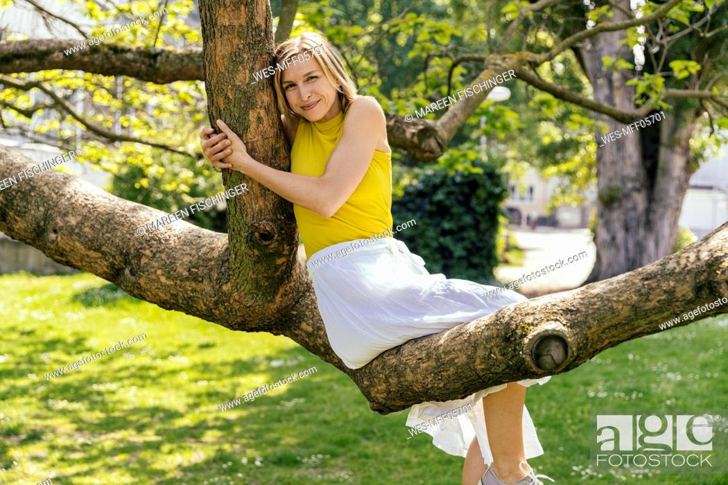 Imagen: Portrait of smiling woman sitting in a tree in a park.