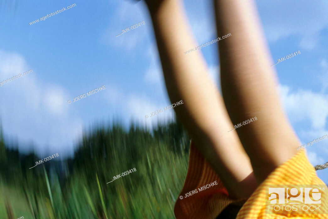 Stock Photo: A girl, 5-10 years old, swinging outside in the garden in summer, blurred.
