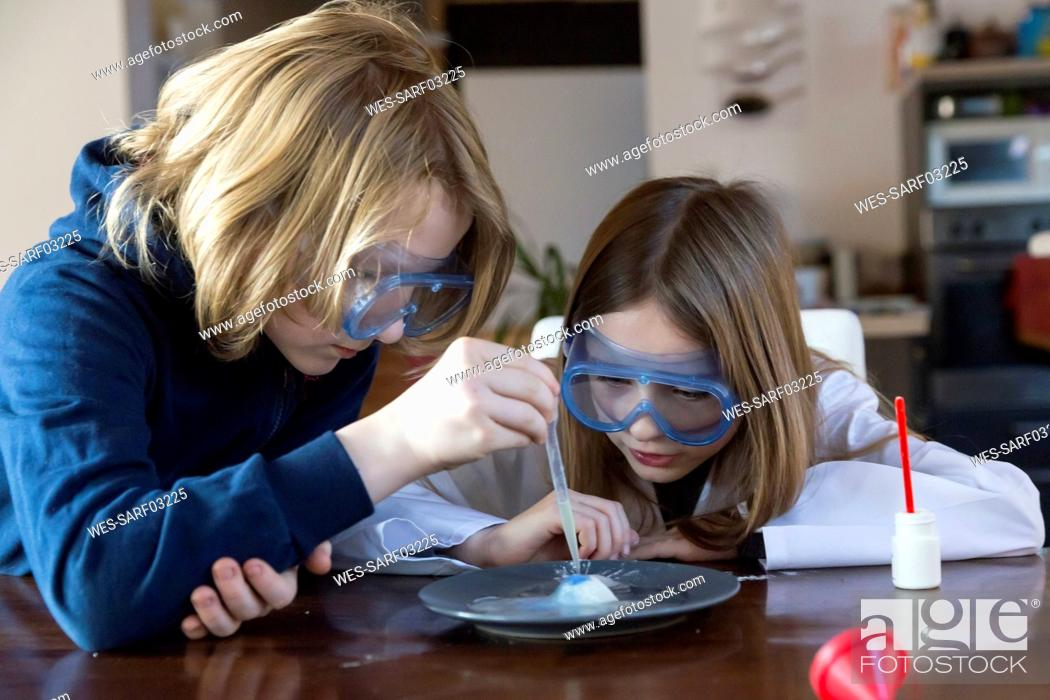 Imagen: Two children wearing safety glasses using chemistry set at home.