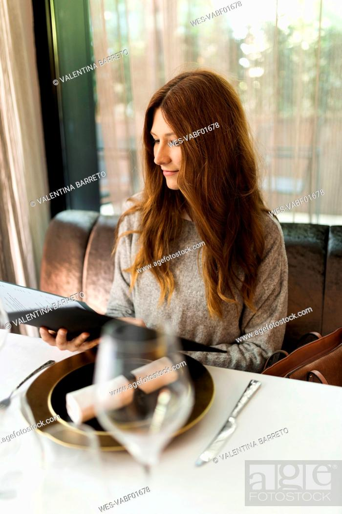 Stock Photo: Woman sitting at table in a restaurant reading menu.