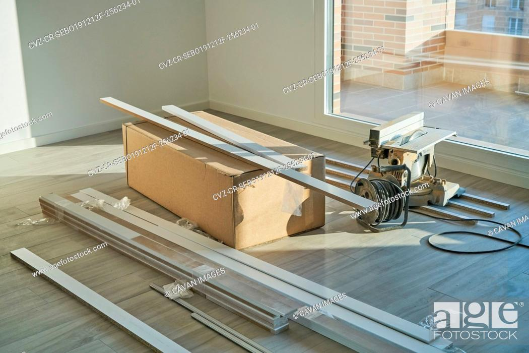 Stock Photo: Spacious empty floor living room with a stack of boxes and reform tables. Housing preparing to furnish.