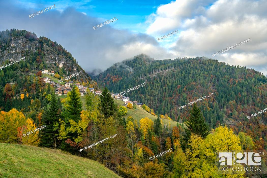 Stock Photo: Colourful aumtumn view across the Cordevole valley with the villages of Pecol and Piaia in the background in Belluno, Italy.