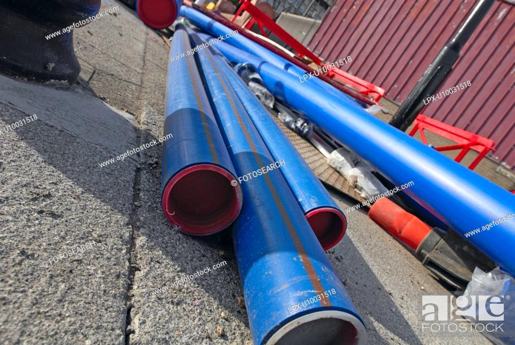 Stock Photo: Utility pipes laying on the pavement.