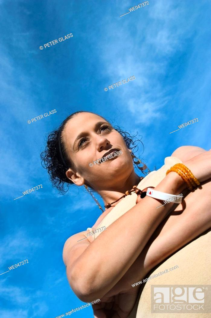 Stock Photo: Young Hispanic woman, eight months pregnant, posing with crossed arms.