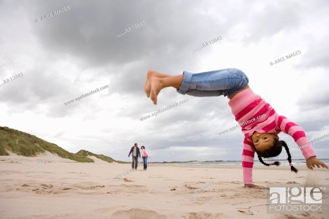 Stock Photo: Girl 7-9 doing handstand on beach, portrait.