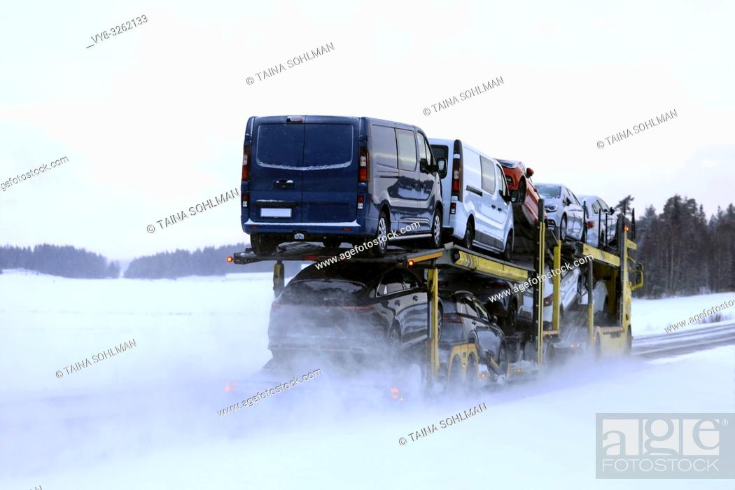 Stock Photo: Car carrier truck transports a load of vehicles on a day of winter snowfall, rear view. Salo, Finland. January 18, 2019.