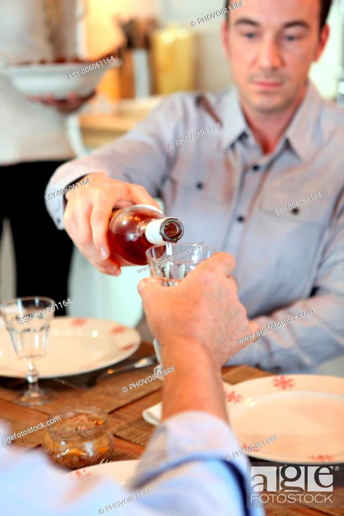 Stock Photo: Man pouring wine during meal.