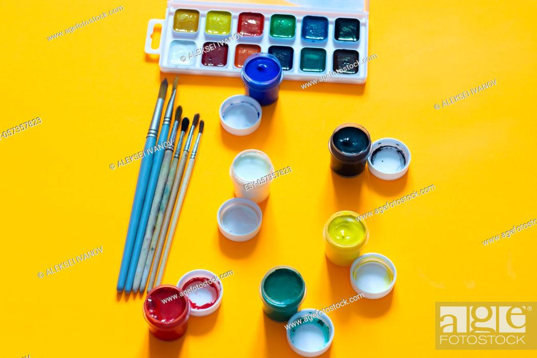 Stock Photo: Brushes, jars of gouache and watercolor paints lie on a yellow background.