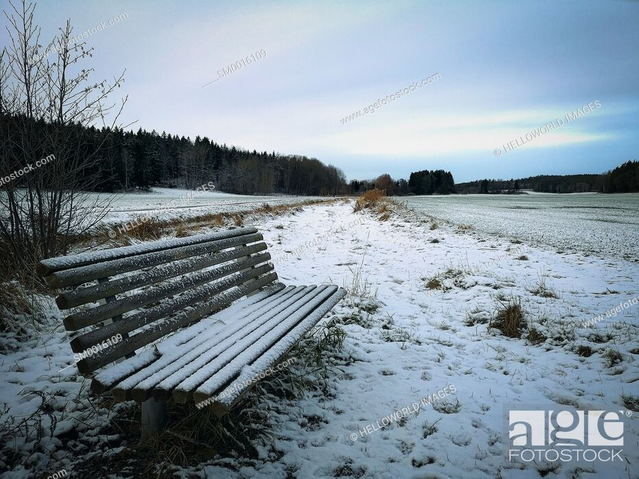 Photo de stock: Ice and frost covered frozen bench seat in snow covered landscape, Sweden.
