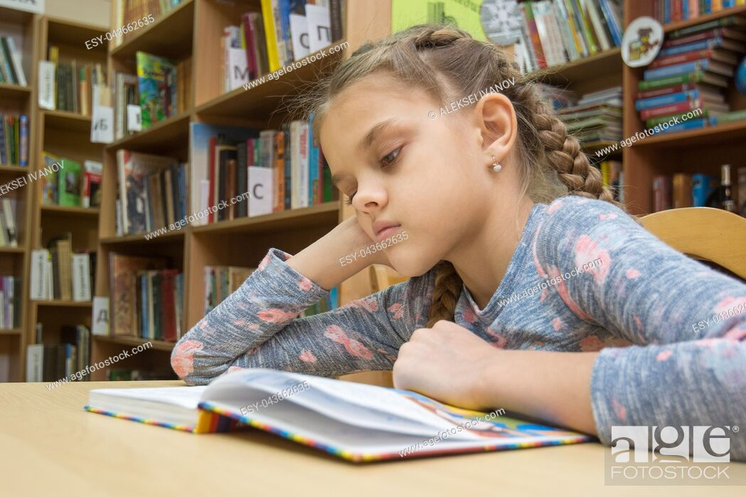 Stock Photo: A girl of ten years old is reading a book in the reading room.