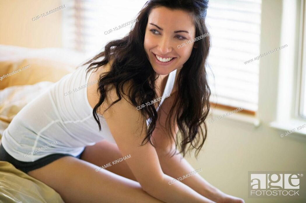 Stock Photo: Woman sitting on edge of bed laughing.
