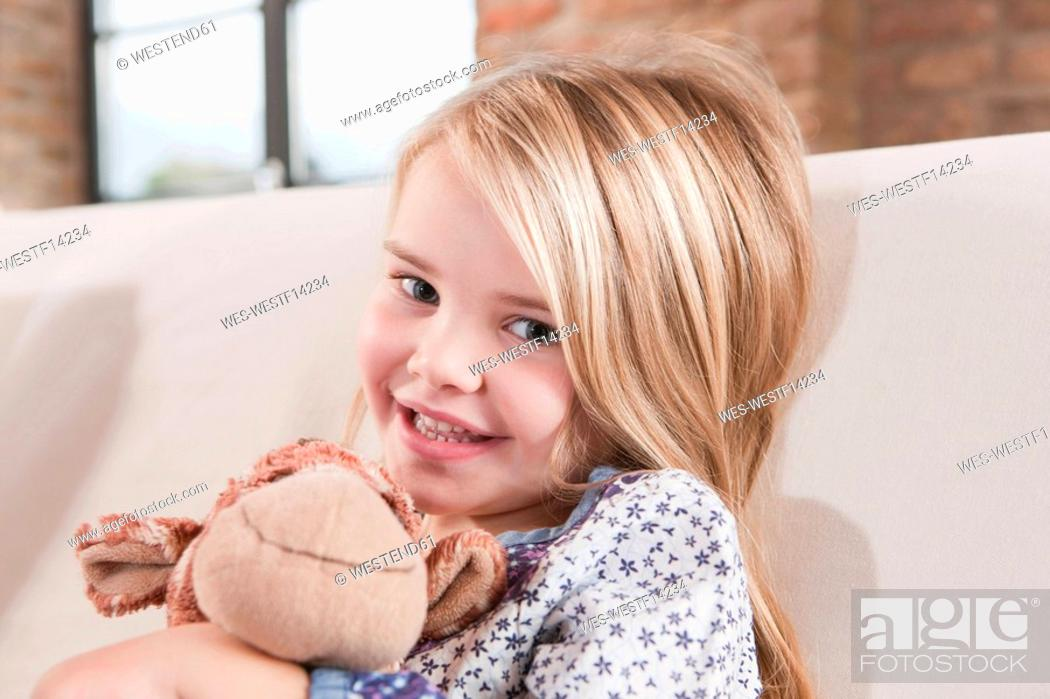 Stock Photo: Germany, Cologne, Girl 4-5 with a stuffed toy, sitting on sofa.