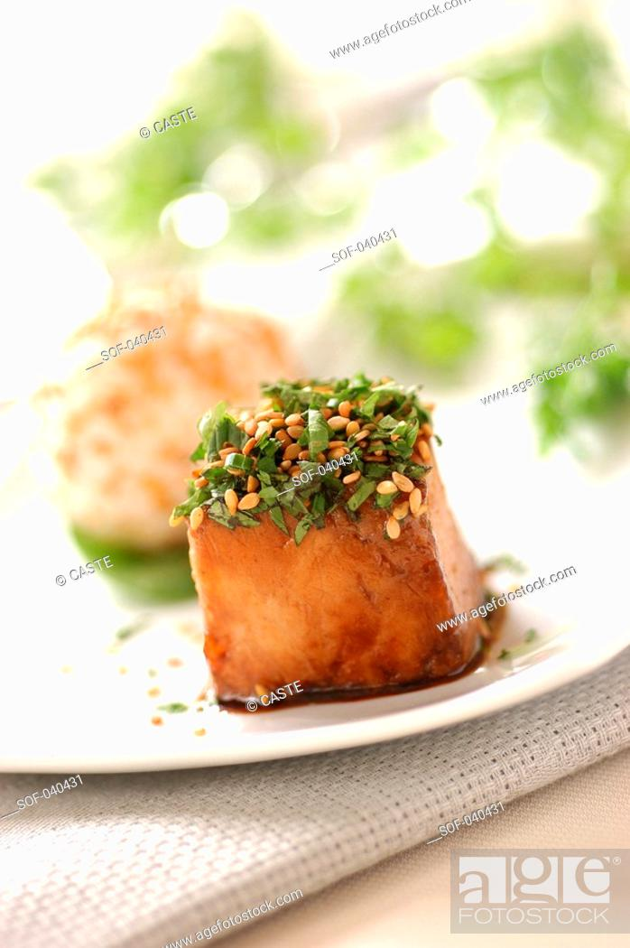 Stock Photo: cube of caramelized grouper fish with soya and honey, topped with herbs and sesame seeds.