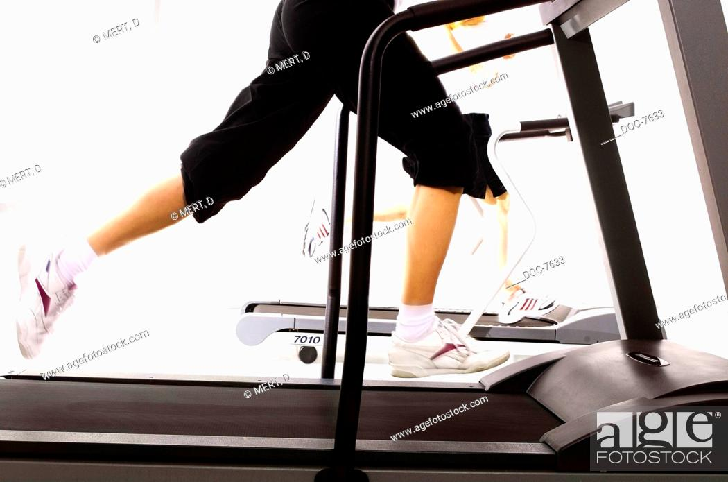 Stock Photo: Woman at strength practice at the treadmill in the gym.