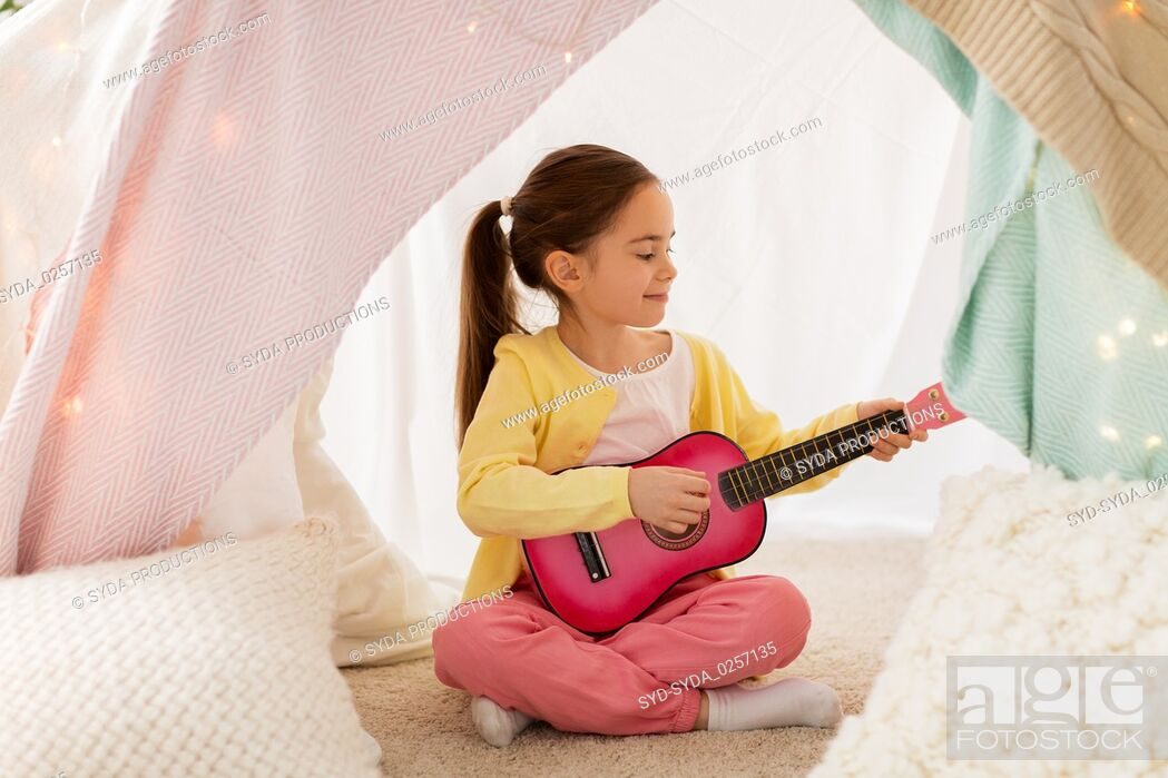 Stock Photo: girl playing toy guitar in kids tent at home.