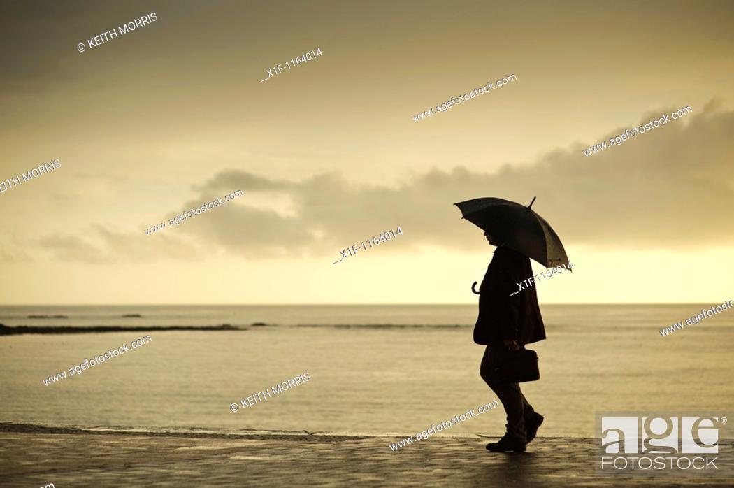 Stock Photo: A man sheltering under an umbrella on a wet summer evening, Aberystwyth Wales UK.