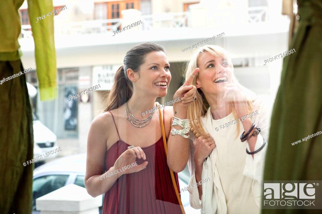Stock Photo: Two women window shopping outside a store.