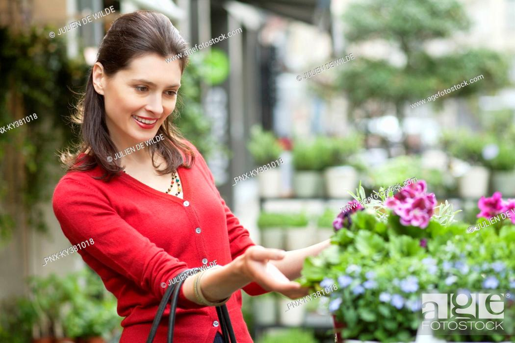 Stock Photo: Close-up of a woman looking at flowers in a flower shop.