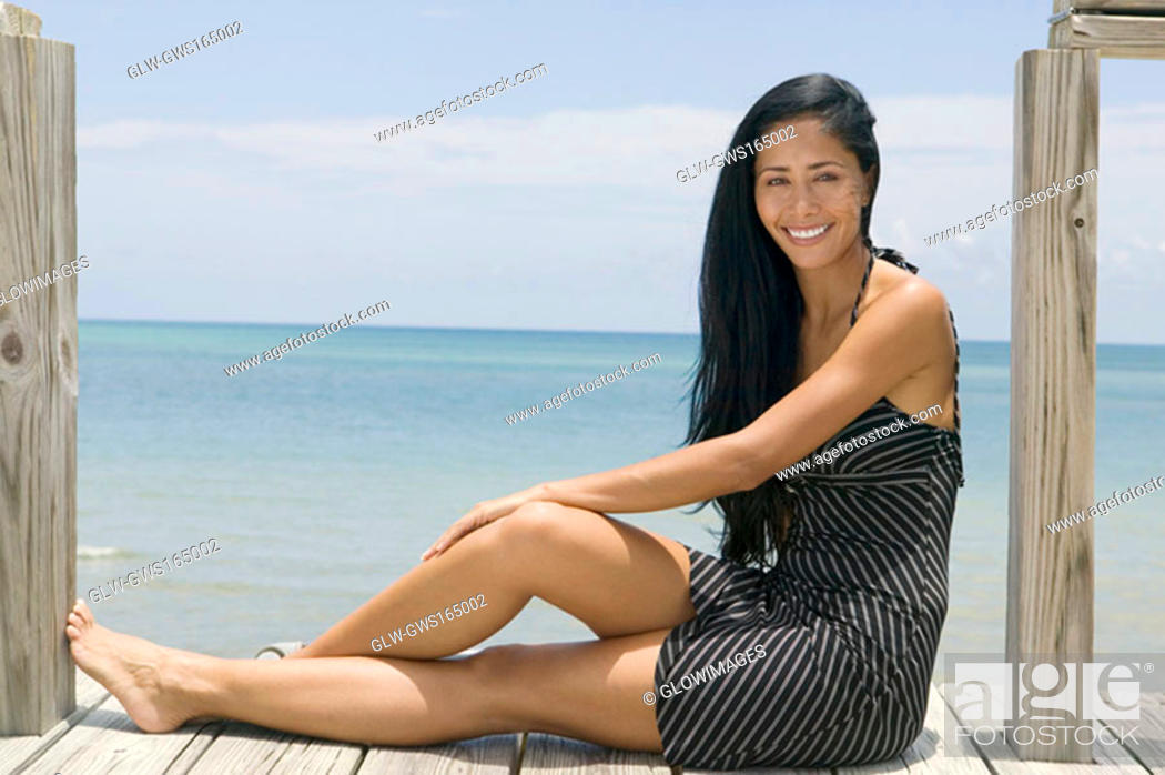 Stock Photo: Portrait of a young woman sitting on a pier and smiling.