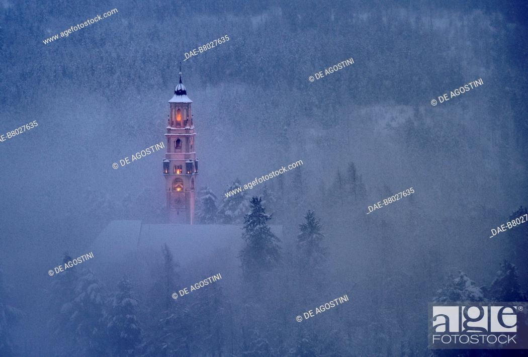 Imagen: The lighted bell tower of the church of the Assumption of Mary, amidst snow and fog, Cavalese, Fiemme Valley, Trentino-Alto Adige, Italy, 17th century.